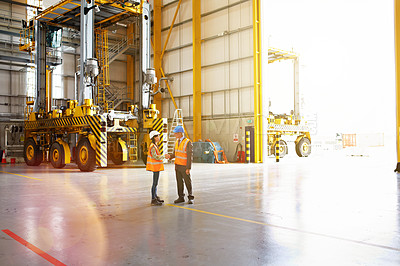 Buy stock photo Shot of two warehouse workers shaking hands together inside of a large warehouse