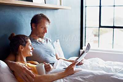 Buy stock photo Shot of a content mature couple reading the newspaper and drinking coffee while lying on their bed