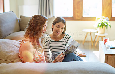 Buy stock photo Shot of two young friends sitting on the living room floor reading a magazine and talking together