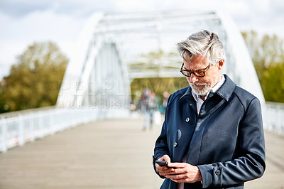 Buy stock photo Shot of a handsome mature man using a cellphone while standing on a bridge in the city