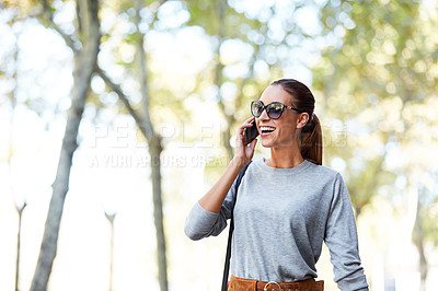 Buy stock photo Shot of a stylish young woman talking on a cellphone while walking in the city