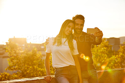 Buy stock photo Shot of a smiling couple taking a selfie together while standing on a balcony overlooking the city