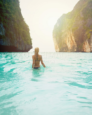 Buy stock photo Rear view shot of a beautiful young woman in a swimsuit walking into the ocean