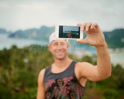 Buy stock photo Shot of a happy young man taking a selfie with his smartphone while enjoying an island vacation