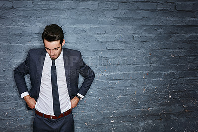 Buy stock photo Shot of a businessman adjusting his pants against a grey wall