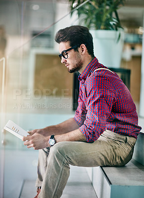 Buy stock photo Cropped shot of a handsome young designer looking at paperwork in his office