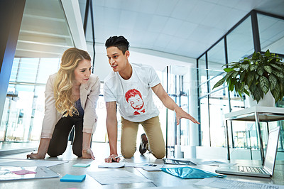 Buy stock photo Shot of two colleagues having a brainstorming session on the floor in a modern office