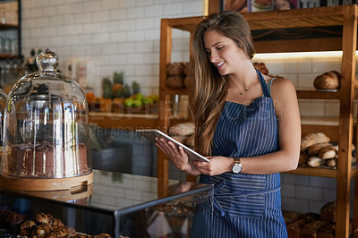 Buy stock photo Cropped shot of a young business owner using a digital tablet in her bakery