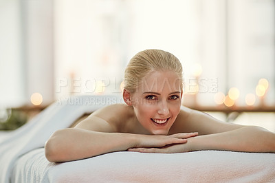 Buy stock photo Portrait of a young woman relaxing on a massage table at a spa
