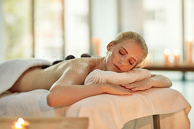 Buy stock photo Cropped shot of a young woman enjoying a hot stone massage at a spa