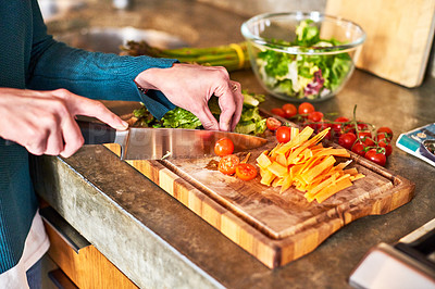 Buy stock photo Closeup shot of a woman chopping vegetables on her kitchen counter