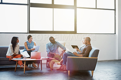 Buy stock photo Shot of a group of coworkers talking together in a modern office