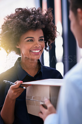 Buy stock photo Shot of a happy businesswoman signing for a package delivered by a courier in her office