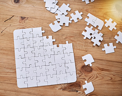 Buy stock photo High angle shot of an unfinished jigsaw puzzle lying on a wooden table