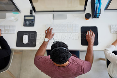 Buy stock photo Shot of a young call centre agent working at his desk