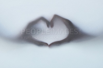 Buy stock photo Defocussed shot of two hands making a heart gesture against a plain background