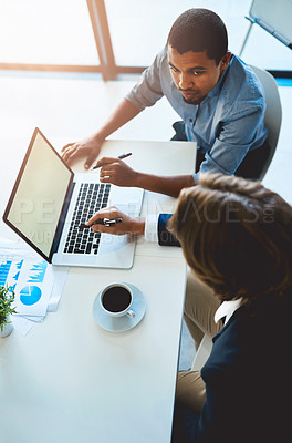 Buy stock photo High angle shot of two young colleagues using a laptop together in the office