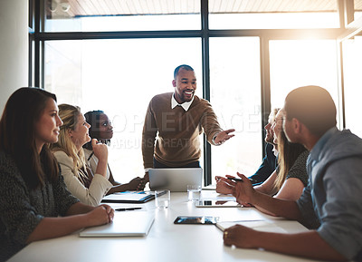 Buy stock photo Shot of a young businessman leading his team in a meeting in the office