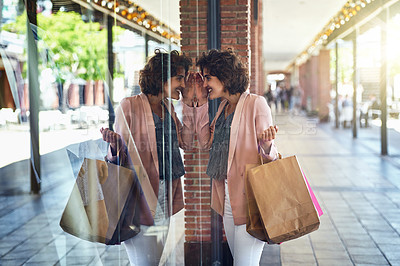Buy stock photo Shot of a woman peering through a shop's window while out on a shopping spree