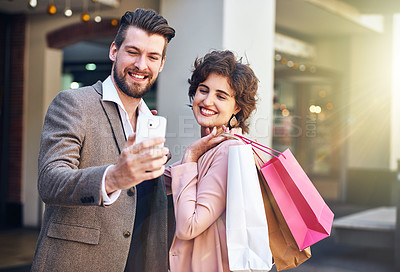 Buy stock photo Shot of a young couple taking a selfie while out shopping