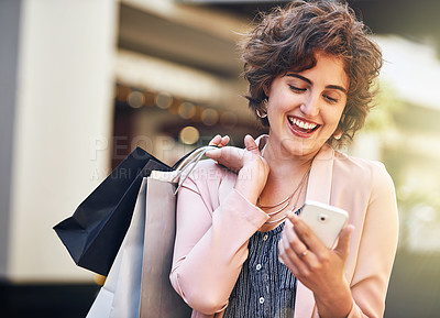 Buy stock photo Shot of a young woman carrying shopping bags and reading a text on her phone