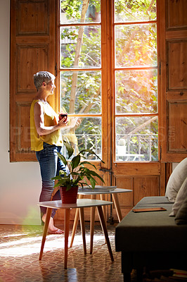 Buy stock photo Shot of a mature woman standing by a window at home drinking a cup of coffee
