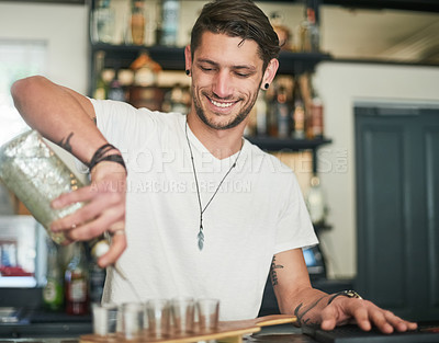 Buy stock photo Shot of a happy young bartender pouring shots behind the bar
