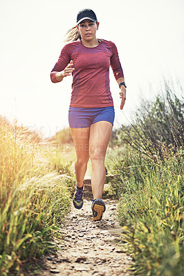 Buy stock photo Shot of a focused young woman running alone outside on a trail