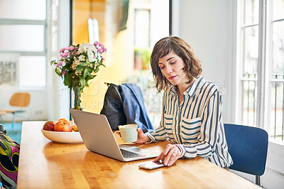 Buy stock photo Portrait of a young woman checking her cellphone while sitting at her kitchen table working on a laptop