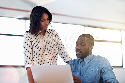 Buy stock photo Shot of two colleagues talking together over a laptop in an office