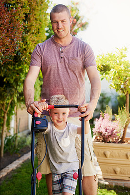 Buy stock photo Portrait of a father and his little son mowing the lawn together at home
