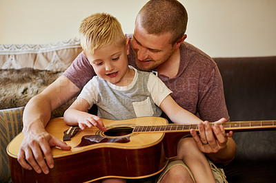 Buy stock photo Cropped shot of a father and his little son playing the guitar together at home