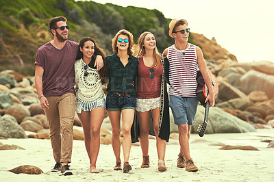 Buy stock photo Full length shot of a group of friends walking on the beach on a summer's day