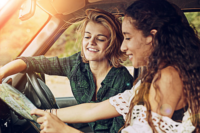 Buy stock photo Cropped shot of two young friends reading a map while on a roadtrip together