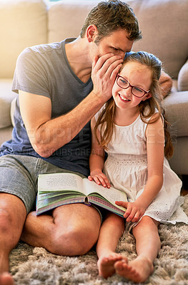 Buy stock photo Cropped shot of a father whispering in his little daughter's ear at home
