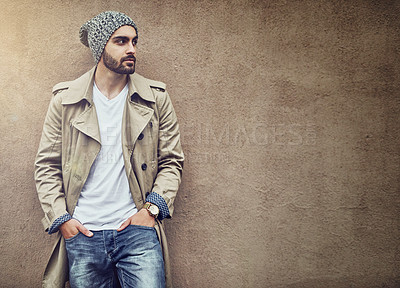 Buy stock photo Shot of a fashionable young man wearing urban wear and posing against a brown wall