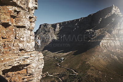 Buy stock photo Shot of a young man standing on the edge of a mountain cliff overlooking a valley