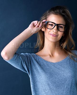 Buy stock photo Studio portrait of a cute teenage girl in glasses posing against a dark background