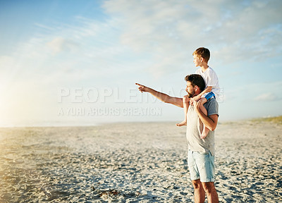 Buy stock photo Shot of a happy father carrying his son on his shoulders on the beach