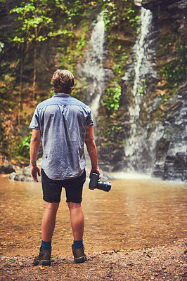 Buy stock photo Rearview shot of a young photographer admiring a waterfall in the jungle