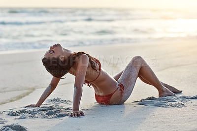 Buy stock photo Shot of a beautiful young woman sitting on the beach
