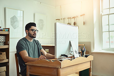 Buy stock photo Cropped shot of a handsome young designer working on his computer in the office