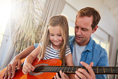 Buy stock photo Shot of a father and his young daughter sitting together in the living room at home playing guitar