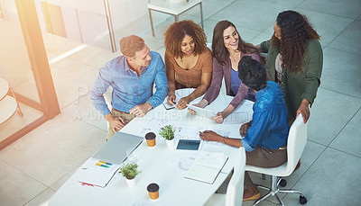 Buy stock photo Shot of a group of designers gathering around a woman using a tablet in a meeting