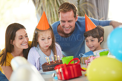 Buy stock photo Shot of a little girl blowing out the candles of her birthday cake surrounded by her family