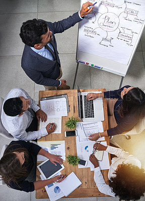 Buy stock photo High angle shot of a group of businesspeople having a meeting around a table