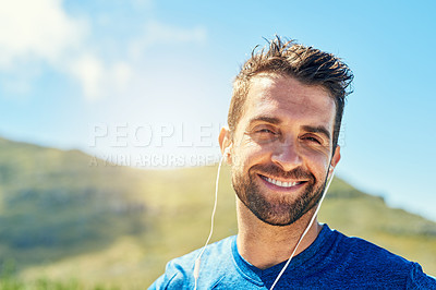 Buy stock photo Portrait of a young man listening to music while out for a run