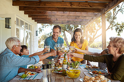 Buy stock photo Shot of a happy family toasting with wine during a family lunch outdoors