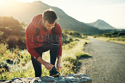 Buy stock photo Shot of a focused young man tying his laces in preparation for a morning run