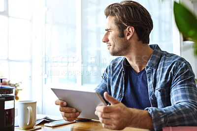 Buy stock photo Shot of a handsome young man working on his tablet at home
